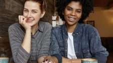 Same-sex lesbian couple hold hands in this stock photo
