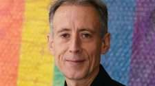 Veteran UK gay rights campaigner Peter Tatchell against a rainbow background
