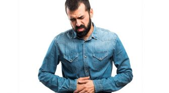 A man clutches his stomach in pain and discomfort in this stock photo