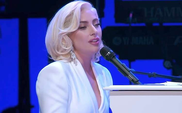 Lady Gaga performs at a piano on stage in this screenshot