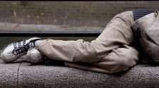 A homeless person lies on the concrete in this stock photo