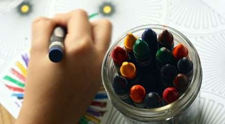 A young person colours using a rainbow spectrum of crayons