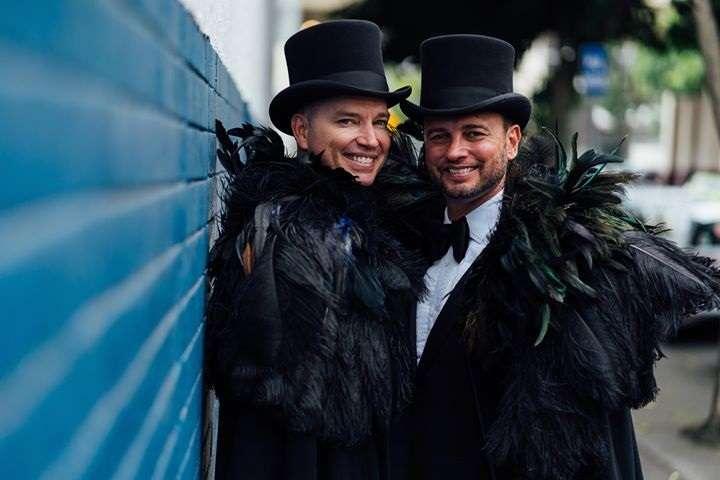 Brad and scott wear feather boas for their wedding