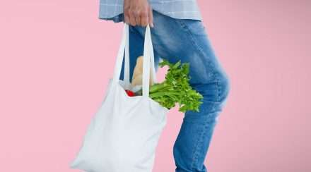 man holding shopping bag pink gender roles study stock photo