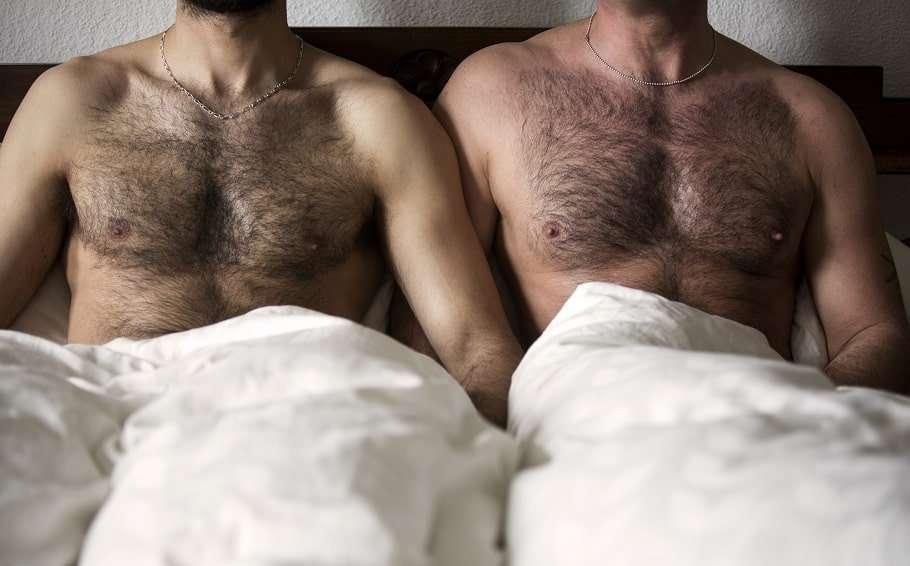 two hairy men in bed stock photo covid-19 coronavirus gay prep hiv prevention